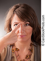 EFT tapping points - Woman doing EFT on the end of eyebrow...