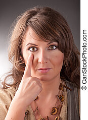 EFT tapping points - Woman doing EFT on the under eye point....