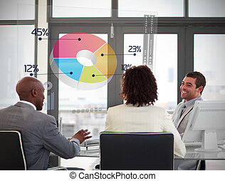 Smiling business people using colorful pie chart on futuristic interface in a meeting