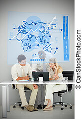 Three business people using blue map diagram interface while...