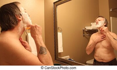 morning shave - man shaving in the mirror