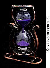 Hourglass with purple sand in a metal frame