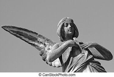 statue of angel holding a cross
