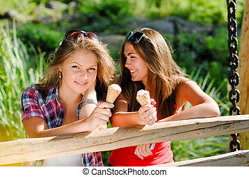 Two happy girl friends eating ice cream outdoors - Two happy...