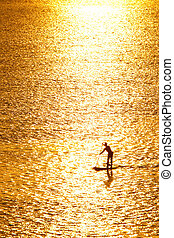 paddleboarding in sunset - man paddleboarding in open water...