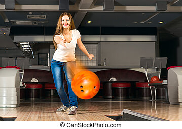 pleasant young woman throws a bowling ball, looks at the...