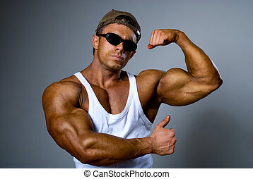 A strong man in sunglasses shows his muscles. Trained body....