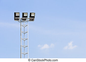 Floodlight with metal pole against blue sky