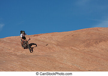 Descent - A lone rider drops down a steep section of...