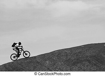 Ascent - A lone mountainbiker rides a steep section of Moads...