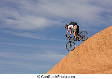 Down - A fearless mountain biker drops down a steep section...