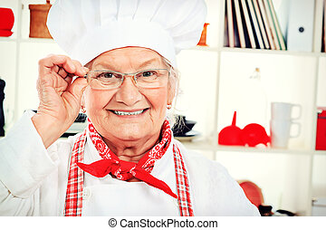home cooking - Portrait of a senior woman chef cook in the...