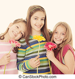 group of happy smiling little girls holding flowers on pale...