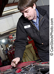 Automotive Technician Works Under the Car Hood in Auto...
