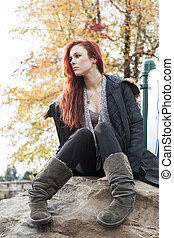 Young Woman with Beautiful Auburn Hair Posed on a Rock -...