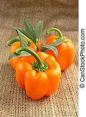 Red sweet pepper - Orange sweet pepper with leaves on a...