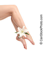 Beautiful woman legs with ankles crossed with a white flower...