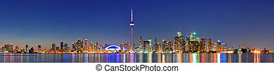 Toronto cityscape panorama at dusk over lake with colorful...