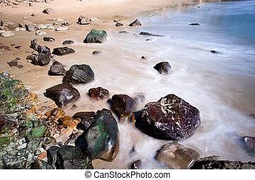 California Beach - A rocky beach shoreline with blurred...