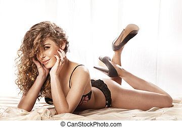 Happy young beautiful woman with long curly hair lying in...