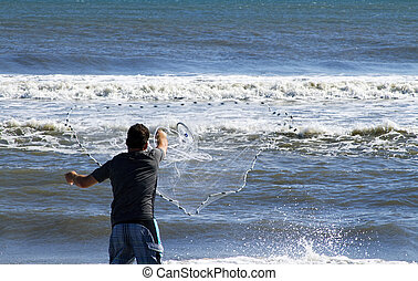 Man Casting Fishing Net - Man casting net into ocean to...