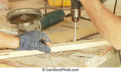 Drilling of wooden beams. Drilled through a wooden board and...