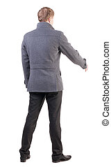 back view of businessman in coat reaches out to shake hands....