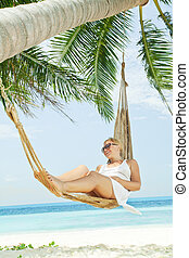 in tropic - view of nice young lady swinging in hummock on...