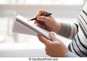 Closeup of Businessman writing in notepad - Businessman...