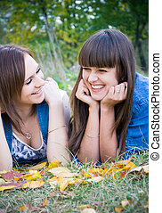 Two girls lying in autumn leaves