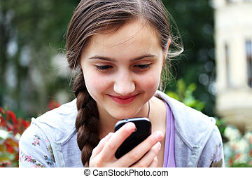 Happy girl with a mobile phone reads the message