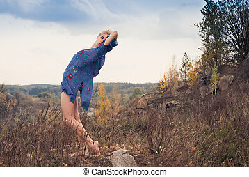 Young happy short haired blond woman trying to touch the sky