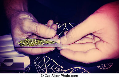 Rolling a Marijuana Joint Lomo Style - Close up at the hands...