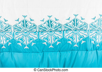 Embroidered white snowflakes on white-turquoise fabric