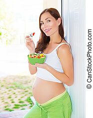 Pregnant female eating salad