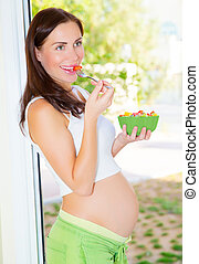 Pregnant girl eating salad