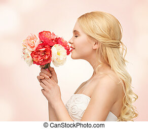 woman smelling bouquet of flowers - picture of young woman...