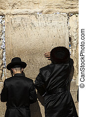 Seeking God - Three orthodox Jewish young adult pressed in...