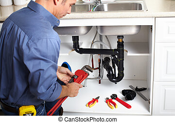 Plumber. - Young smiling plumber fixing a sink in the...