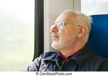 Relaxed old man sitting near the window in the carriage