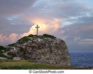 cross on mountain top - colorful coastal sundown scenery on...
