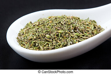 Oregano in white spoon on black table