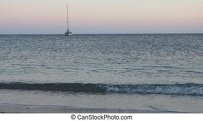 Seashore dusk - Seashore at sunset with a sailboat