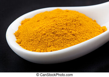 Curcuma powder - curcuma powder in white spoon on black...