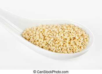 Sesame seeds in the spoon on white background