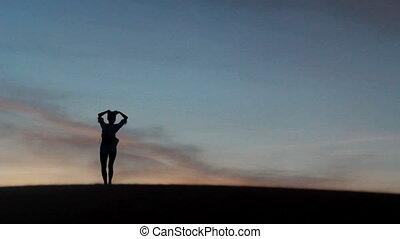 Beautiful woman dancing in desert