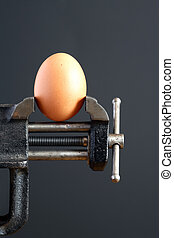 Pressure concept Hens egg pressured in a bench vice on dark...