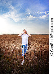 Happy man standing with closed arms on a wheat field