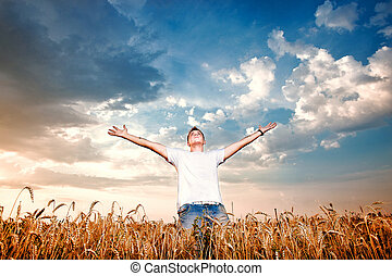 Happy man standing with open arms on a wheat field
