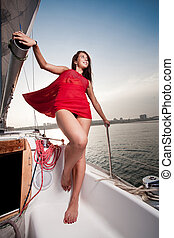 pretty young woman in red dress posing on the yacht